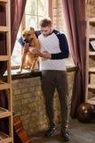 El hombre abraza su perro que hace una pausa la ventana Fotos de archivo