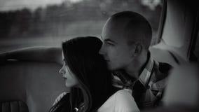 El hombre abraza a una mujer en un coche, pero ella da vuelta lejos al bw metrajes