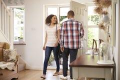 El hombre abre el hogar de Front Door For Woman Returning del trabajo Foto de archivo