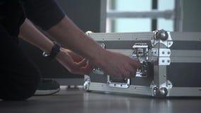 El hombre abre la caja de aluminio del sistema del viaje de DJ Equipo de mezcla audio portátil del estudio en la caja metálica almacen de metraje de vídeo
