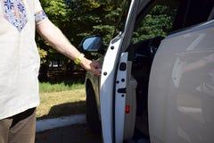 El hombre abre la puerta de coche foto de archivo libre de regalías