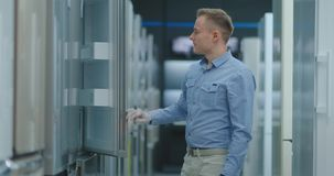 El hombre abre la puerta del refrigerador en la tienda de dispositivos y compara con otros modelos para comprar la nueva casa metrajes