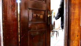 El hombre abre la puerta vieja y entra en el sitio brillante almacen de metraje de vídeo