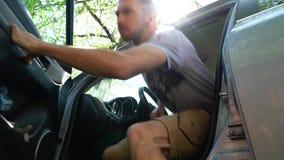 El hombre abre la puerta y sale del coche almacen de metraje de vídeo