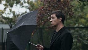 El hombre abre el paraguas almacen de video