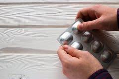 El hombre abre un paquete de tabletas de los antibióticos Imagenes de archivo