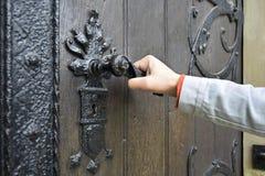 El hombre abre una puerta de madera antigua adornada con los elementos del hierro labrado imagen de archivo libre de regalías