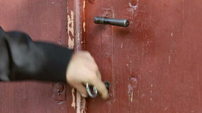 El hombre abre una puerta de madera vieja con una llave enorme del hierro almacen de video