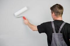 El hombre acabó la pintura de pared, aislada en gris Imágenes de archivo libres de regalías