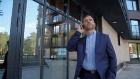 El hombre acertado cerca del centro de negocios habla en el teléfono almacen de video