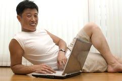 El hombre acertado joven con el ordenador se sienta Imagen de archivo