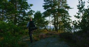 El hombre activo con la mochila grande camina en la montaña por el mar en la puesta del sol almacen de metraje de vídeo