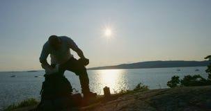 El hombre activo con la mochila grande toma una rotura en el bosque por el mar en la puesta del sol almacen de metraje de vídeo
