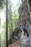 El hombre activo está subiendo en una pared de la roca foto de archivo