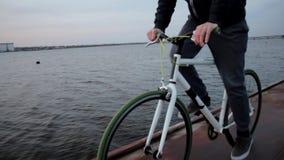 El hombre activo joven monta la bicicleta del deporte, igualando paisaje del río, forma de vida sana almacen de metraje de vídeo