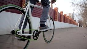 El hombre activo joven monta la calle vacía de la bici del deporte abajo, forma de vida al aire libre sana almacen de video