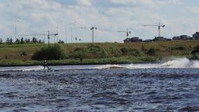 El hombre activo monta juguetónamente waterski en el barco de motor de siguiente de la velocidad a lo largo del río metrajes