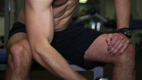El hombre acumula los músculos que levantan una pesa de gimnasia en el gimnasio almacen de video
