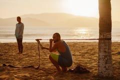El hombre adolescente está estirando slackline en la playa Fotos de archivo libres de regalías