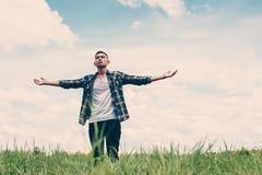 El hombre adolescente joven de la libertad que estira sus brazos en el cielo goza Fotos de archivo libres de regalías