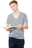 El hombre adolescente joven está leyendo un libro Imagen de archivo