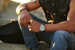 El hombre adolescente joven lleva el reloj elegante con la pantalla táctil Foto de archivo