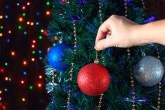 El hombre adorna las bolas del árbol de navidad Foto de archivo libre de regalías