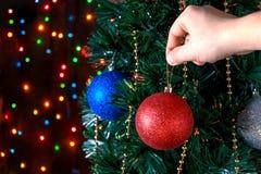 El hombre adorna las bolas del árbol de navidad Imagen de archivo