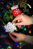 El hombre adorna un árbol de navidad con los juguetes Fotos de archivo libres de regalías