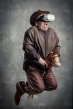 El hombre adulto caucásico mayor goza el experimentar de la simulación immersive del juego del vaquero de la realidad virtual Con Foto de archivo libre de regalías