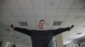El hombre adulto con exceso de peso realiza la crianza con pesas de gimnasia almacen de metraje de vídeo