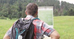 El hombre adulto con una mochila lee indicadores en las montañas metrajes