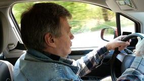 El hombre adulto conduce su coche, da vuelta al volante y anticipa con sorpresa almacen de metraje de vídeo
