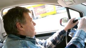 El hombre adulto conduce su coche, da vuelta al volante y anticipa con sorpresa metrajes
