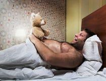 El hombre adulto en cama mira el oso del juguete imagen de archivo libre de regalías