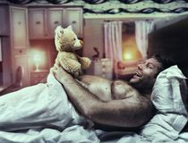El hombre adulto en cama mira el oso del juguete imagenes de archivo