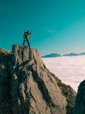 El hombre adulto entonado de la imagen con la mochila se coloca al borde de un acantilado y mira en la distancia contra el cielo  Fotografía de archivo