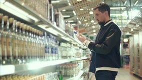 El hombre adulto está consiguiendo la botella con una vodka del estante de la licorería almacen de video