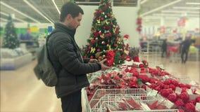 El hombre adulto está escogiendo los ornamentos para el árbol de navidad en un supermercado metrajes
