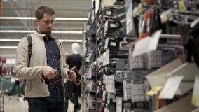 El hombre adulto está examinando un simulador de los deportes de la mano para entrenar en una tienda del deporte almacen de video