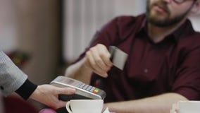 El hombre adulto está llamando a un camarero y está pagando la cuenta con su tarjeta de crédito almacen de metraje de vídeo