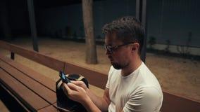 El hombre adulto está mirando imágenes en teléfono móvil, se sienta solamente por la tarde al aire libre almacen de video