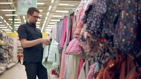 El hombre adulto está mirando una chaqueta caliente para su niño en una tienda de ropa almacen de metraje de vídeo