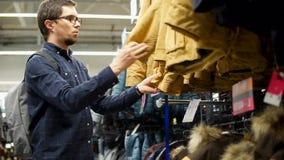 El hombre adulto está mirando y las chaquetas conmovedoras del invierno en un deporte hacen compras con ropa almacen de video