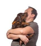 El hombre adulto está sosteniendo su perrito dulce aislado en el backgroun blanco Imagen de archivo