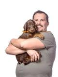 El hombre adulto está sosteniendo su perrito dulce aislado en el backgroun blanco Imagen de archivo libre de regalías