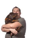 El hombre adulto está sosteniendo su perrito dulce aislado en el backgroun blanco Fotografía de archivo