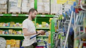 El hombre adulto está tomando el hacha en un pasillo de la tienda, la está examinando y está poniendo detrás en el estante almacen de metraje de vídeo
