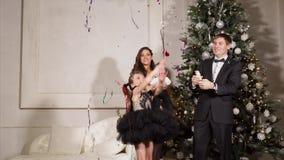 El hombre adulto está utilizando tostadores de palomitas de maíz con confeti en Año Nuevo en el hogar para su familia almacen de metraje de vídeo