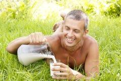 El hombre adulto feliz bebe la leche fresca Foto de archivo